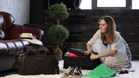 Young woman closing suitcase full of clothes Live Action