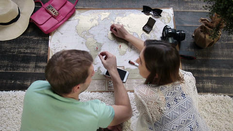 Couple planning new journey with travel map Footage