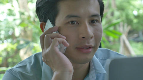 4K : Young Asian business man using laptop and talking with smart phone in cafe Footage