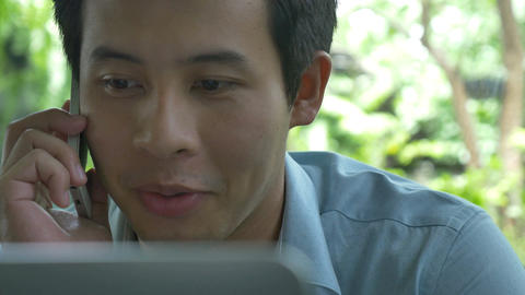 4K : Young Asian business man using laptop and talking with smart phone in cafe ビデオ