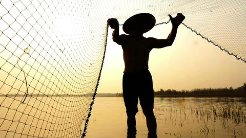Silhouette of traditional fishermen throwing net fishing in the lake at sunrise  Filmmaterial