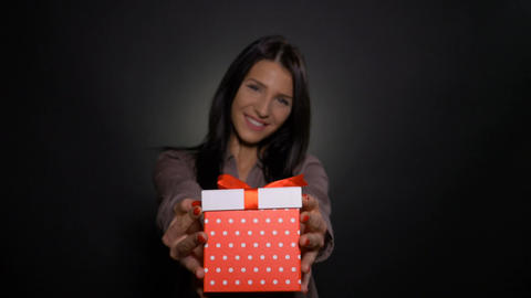 Young beautiful girl smiling and offering a gift box Footage