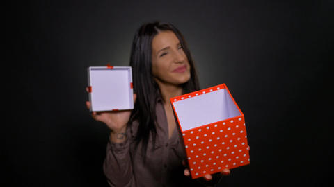 Surprised attractive young woman holding and opening gift box and showing it Footage