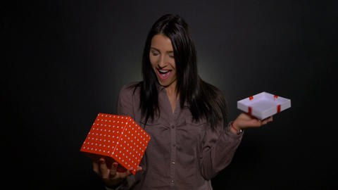 Young woman opening a gift box and getting surprised by the present Footage