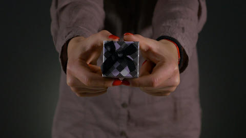 Close up shot of woman hands holding a small gift box wrapped with grey ribbon Footage