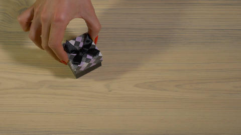 Funny hand of a woman trying to open small gift box placed on a wooden backgroun Footage