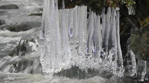 Long icicles hang above dark cold water of mountain river. Icicles glitter above Footage