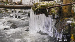 Detail of shinning icicles hanging above cold water of winter mountain river. Gl Footage