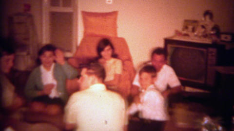 1965: Family playing poker cards crowding together on living room floor. SAN DIE Footage