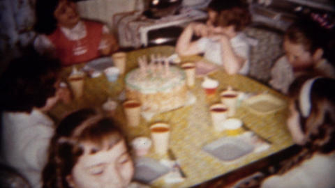1962: Little girl birthday party cake served around kitchen table Footage