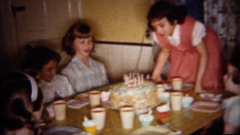 1962: Birthday girl blows out cake candles at home party Footage