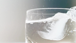 Ice cube fall into cup of water Footage