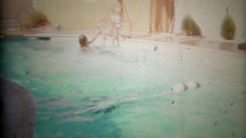 1967: Children diving backwards into personal swimming pool Footage