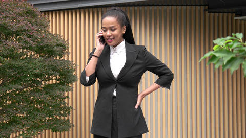 Successful Black Woman Talking On Cell Phone Near Office Building stock footage