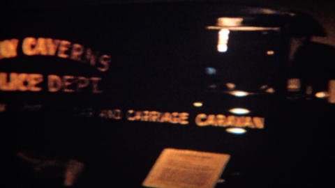 1964: Man visits dark old car museum Luray Caverns police department Footage