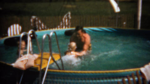 1961: Children jumping into dad's arms in home above ground swimming pool Footage