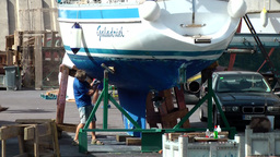 Spain Gran Canary Mogán 032 man repairs boat hull Footage