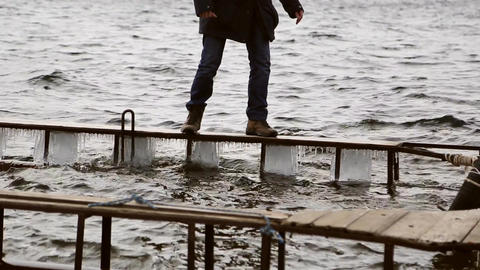 Man walking dangerously on a narrow icy pier Footage