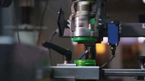 Macro Automated Machine Turns Cap to Bottle with Motor Oil Footage