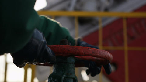 Closeup Worker in Leather Gloves Twists Iron Valve Footage