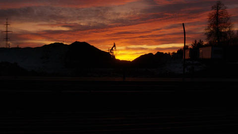 Pumpjack Works against Sunset in Twilight Footage
