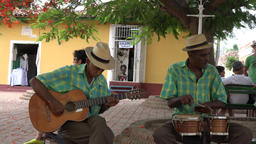 Trinidad, Cuba: Zoom In from musicians to a souvenir painting for sale Footage