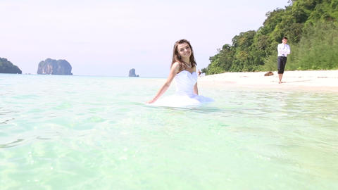 Bride in Wedding Dress Walks in Water and Groom Walks along Beach Footage