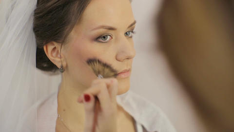 Make up artist applying powder with make up brush to young woman in beauty salon Footage