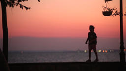 A Kid Walking On Coastal Street At Sunset Footage
