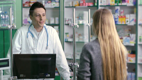 Young pharmacist counseling customer in pharmacy Footage
