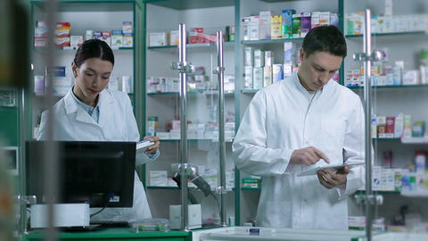 Two pharmacists working in pharmacy drugstore Footage