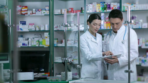 Two pharmacists using digital tablet in pharmacy Footage