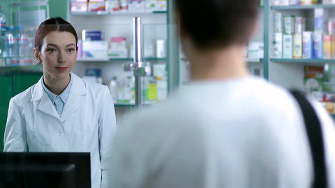 Female pharmacist counseling customer in pharmacy Footage