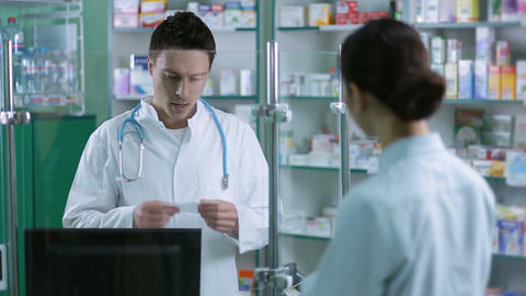 Cheerful male pharmacist reading prescription Footage