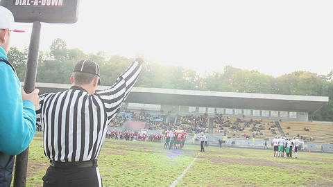 Professional field official makes stalling warning hand sign for football teams Footage