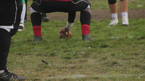 Back view of gridiron player snapping ball to teammate, amateur football game Footage