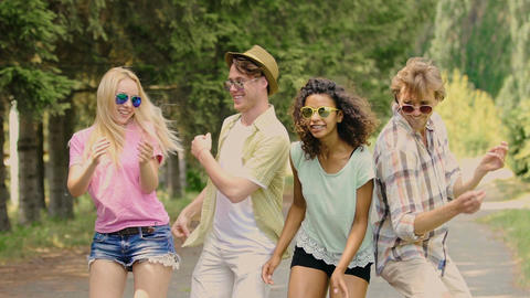 Four multiracial friends enjoying open-air music festival, dancing and jumping Footage