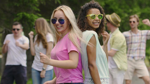 Two young models dancing with friends at music festival, happiness and joy Footage