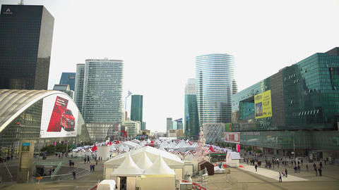 Large tents in city center, street fair, people walk near modern glass buildings Footage