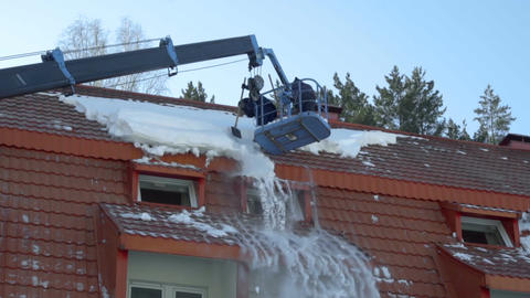 Worker removing snow on the roof of the building Footage