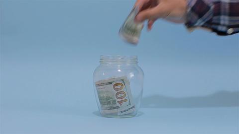 Man Puts American Dollar 100 into a Glass Jar for Storage. Slot glass jar on lig Live Action