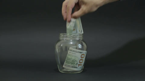 Man Puts American Dollar 100 into a Glass Jar for Storage. Slot glass jar on bla Live Action