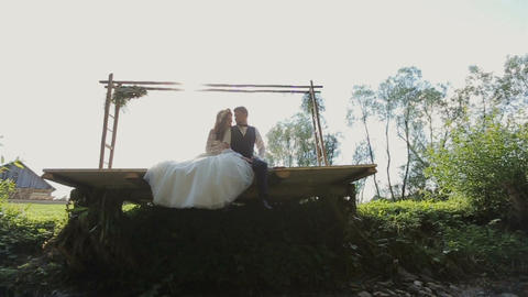 Happy bride and groom sitting hugging and Kissing near river