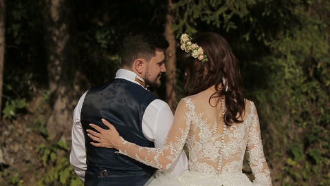 Close-up of Young and in love wedding couple sits hugging near river Footage