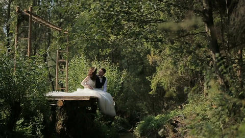 Young and in love wedding couple sits hugging near river