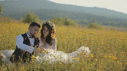 Wedding couple sitting on the field and hugging in the mountains