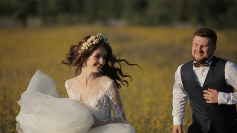 Beautiful bride and groom running on the field in the mountains