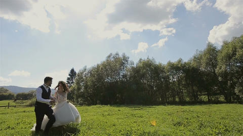 Charming wedding couple running on the grass in the mountains