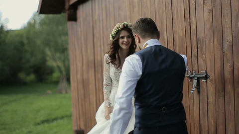 Happy bride and groom running and laughing near wooden ambar at the wedding walk Live Action