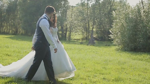 Charming wedding couple walking on the grass in the mountains